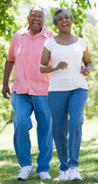 Senior African American couple walk briskly